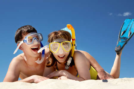 scuba woman: Portrait of cheerful couple in aqualungs lying on sand
