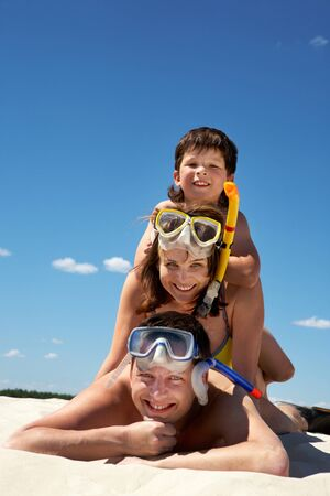 vacation: Portrait of happy family in goggles and flippers lying on sandy beach against blue sky Stock Photo