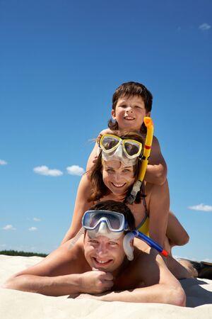 flippers: Retrato de familia feliz en gafas y aletas en la playa de arena contra el cielo azul