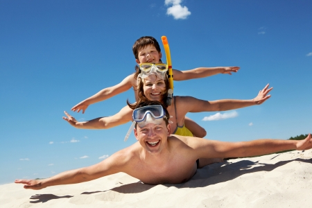 Portrait of cheerful couple and their son lying on sand and looking at camera photo