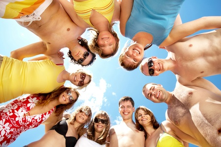 view from below: Below view of circle of friends looking at camera with blue sky above them