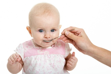 Adorable baby being fed from spoon by her mother hand photo