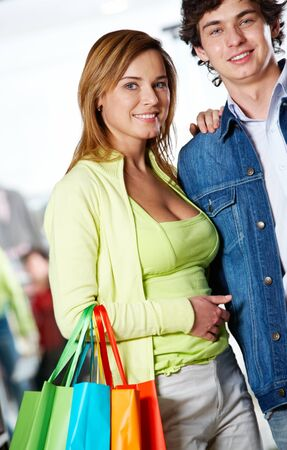 after shopping: Portrait of amorous couple looking at camera with smiles after great shopping