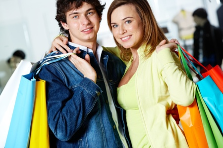 Portrait of loving couple after buying gifts looking at camera with smiles photo