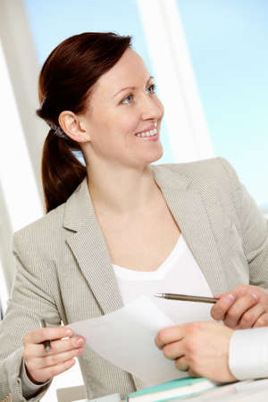 Happy businesswoman during discussion of new business strategy at meeting photo
