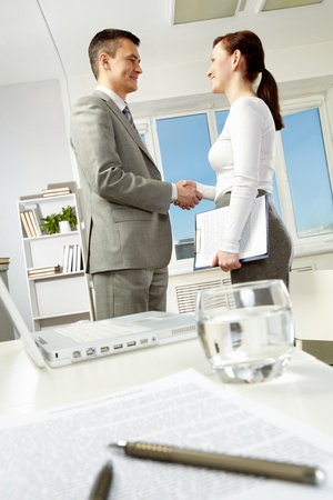 Photo of business partners handshaking after making agreement in office photo