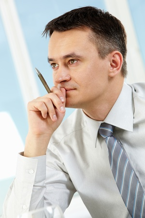 Photo of handsome businessman with pen in hand under inspiration photo