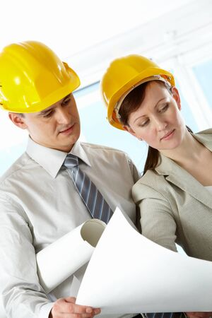 female architect: Portrait of two architects in helmets discussing document at meeting