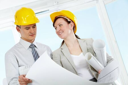 Portrait of two architects in helmets holding blueprint photo