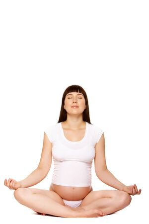 Portrait of pregnant female meditating over white background photo