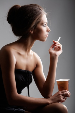 Portrait of elegant female smoking with plastic glass in hand photo
