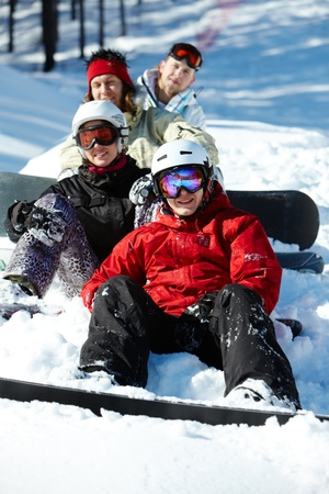 Portrait of happy friends snowboarding during winter vacations photo