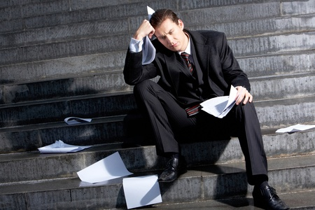 depressed person: Portrait of sad businessman sitting on stairs with papers in hands and lost expression on his face