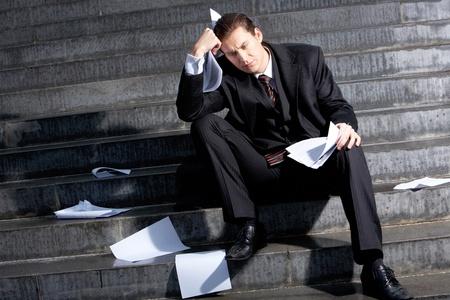 persona deprimida: Retrato de hombre de negocios triste sentado en las escaleras con documentos en la expresi�n perdida en su rostro y manos Foto de archivo