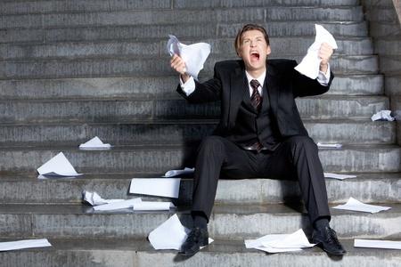 Afbeelding van rouwende zakenman huilen met papieren in handen Stockfoto