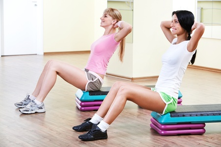 Two girls sitting in the gymnasium and practicing physical exercises Stock Photo - 9725303
