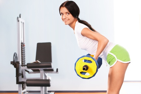 Photo of active girl standing on the floor and lifting dumbbell in the sports club photo