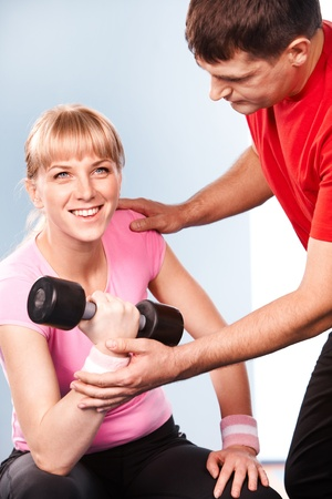 Photo of active girl lifting dumbbell in the sports club with her instructor near by photo