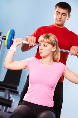 Portrait of sporty girl holding dumbbell assisted by her trainer photo