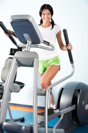 Image of beautiful girl on training apparatus in sport club photo