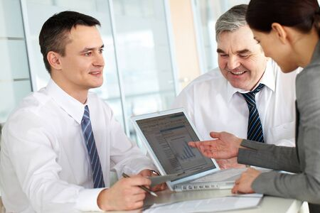 A business team of three sitting at table and planning work Stock Photo - 9725223