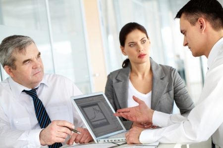 Een zakelijke team van drie zitten aan tafel en planning van werkzaamheden