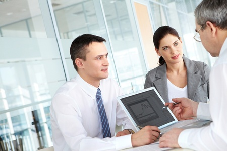 business consulting: A business team of three sitting at table and planning work Stock Photo