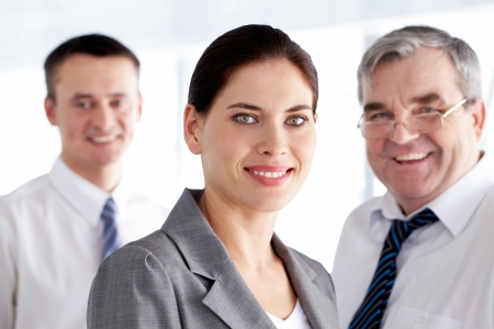A business team with pretty leader in front looking at camera and smiling  Stock Photo - 9725251