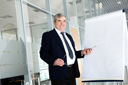 Portrait of elderly teacher pointing at whiteboard in office  photo