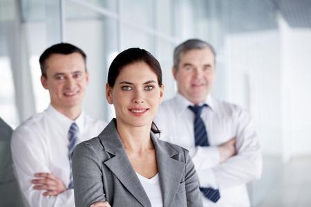 Une équipe de commerciaux avec jolie leader devant regardant la caméra et souriant  Banque d'images