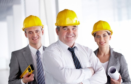 A smiling architect in helmet against his two colleagues  photo