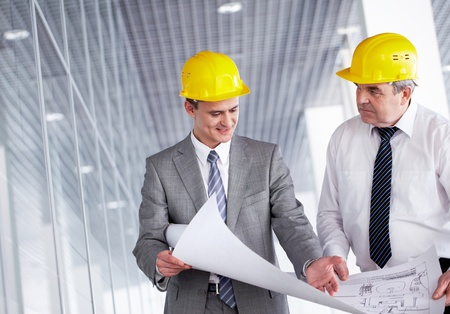 executive helmet: A senior leader looking at camera and smiling with colleague behind Stock Photo