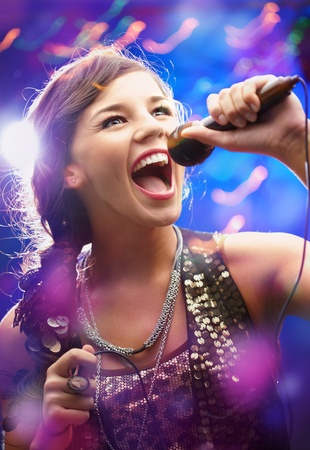 Portrait of a glamorous girl with mike singing song Stock Photo - 9725362