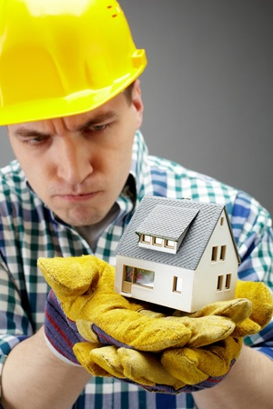 Portrait of a serious architect holding a house model Stock Photo - 9725578