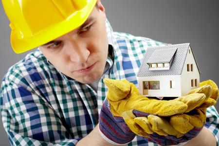 constructeur: Portrait d'un architecte graves tenant un mod�le de maison et regarder