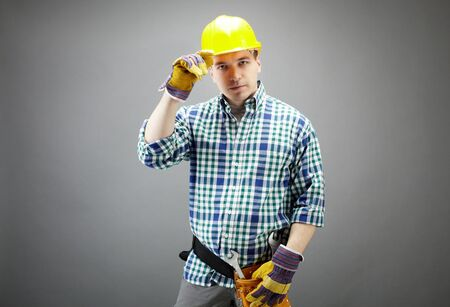 Portrait of confident worker in helmet isolated on grey photo