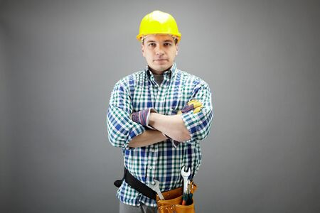 repairman: Portrait of confident worker in helmet isolated on grey