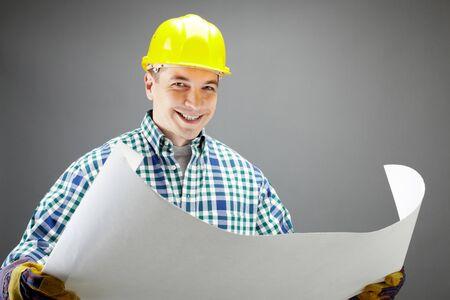 constructeur: Portrait d'un travailleur sourire dans le casque d�tenant un plan