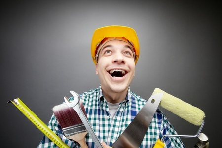 Portrait of happy craftsman with different tools in hands photo