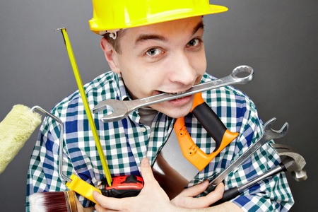 Portrait of happy craftsman with different tools in hands and wrench in mouth photo