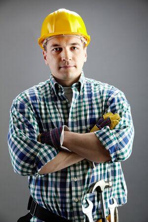 tradesmen: Portrait of confident worker in helmet isolated on grey