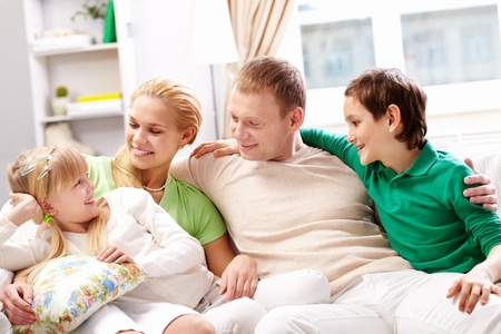 A young family of four sitting on sofa and looking at cute girl Stock Photo - 9725415