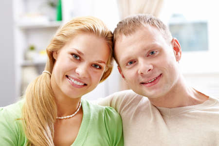 A young couple looking at camera with smiles photo