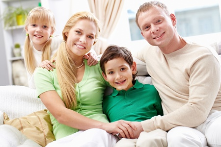 A young family of four sitting on sofa, looking at camera and smiling photo