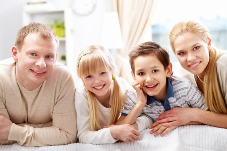 home line: A young family of four looking at camera and smiling