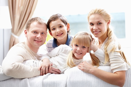 A young family of four looking at camera and smiling photo