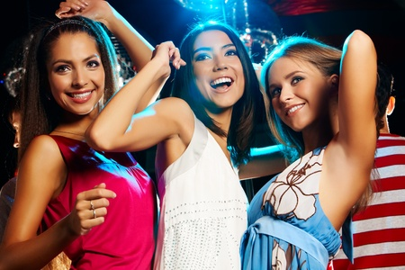 Group of fashionable girls dancing energetically in night club photo