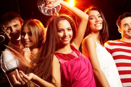 Group of teens dancing in night club with glamorous girl in front photo