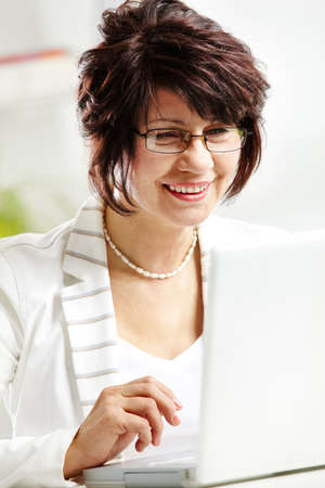 Portrait of middle-aged female typing and looking at laptop display photo