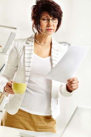 Portrait of middle-aged female reading paper during working day photo